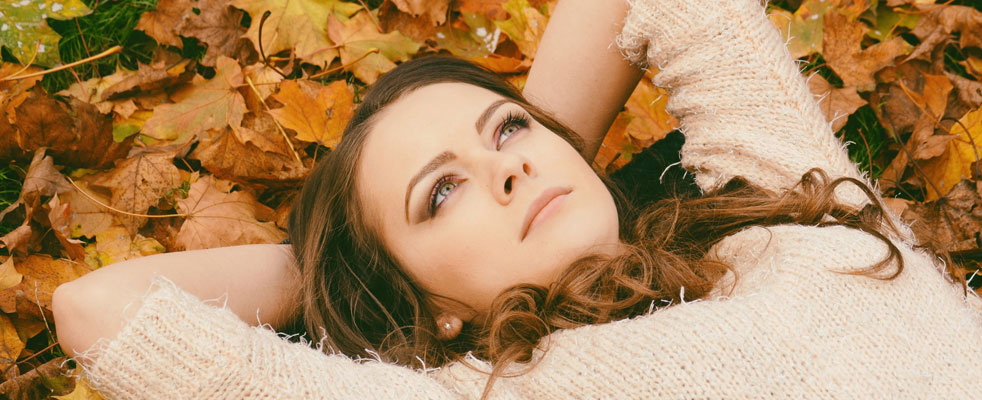 Girl lying in autumn leaves with her hands behind her head